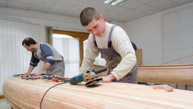 Young carpenters assembling new canoe