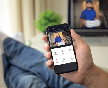 man on sofa holding phone with app smart home on screen in room house; Shutterstock ID 1170412429; Purchase Order: -