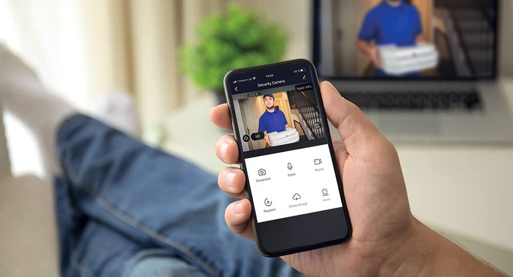 Man-on-the-sofa-using-the-phone-with-app-smarthome-on-the-screen-in-the-living-room-RET